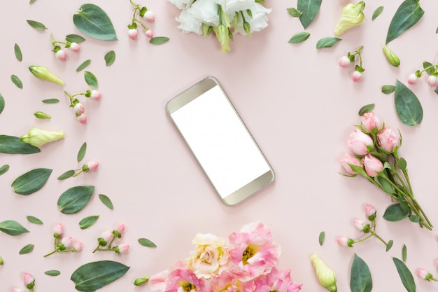 Vista superior da mesa-de-rosa com celular moderno ouro e moldura de flor