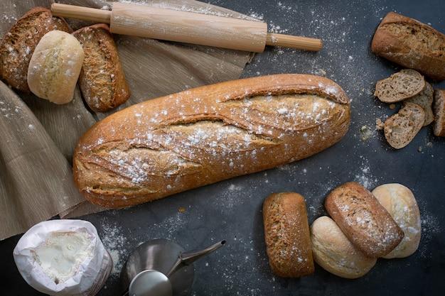 Vista superior da mesa de trabalho ao lado do forno com um pão e alguns pãezinhos frescos