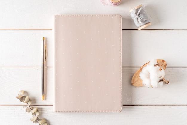 Vista superior da mesa de trabalho branca com caderno de papel em branco, algodão natural. vela plana de natureza morta, clipes de papel dourado para fichário. bloco de notas e caneta.