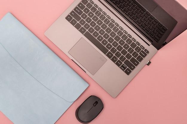 Vista superior da mesa de trabalho branca com laptop moderno, estojo de couro azul para computador pessoal e mouse sem fio. espaço de trabalho para a escola ou escritório. modelo e cópia de espaço. postura plana.
