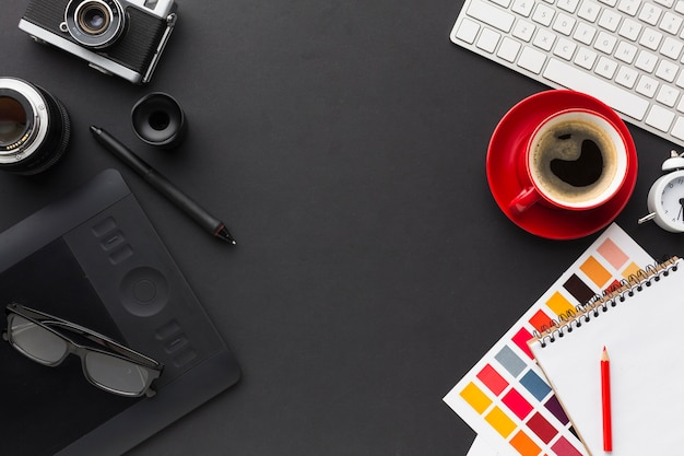 Vista superior da mesa de trabalho com café e bloco de desenho