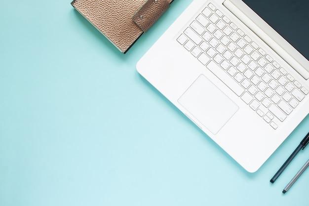 Vista superior da mesa de trabalho com computador portátil branco sobre fundo de cor azul com espaço de cópia