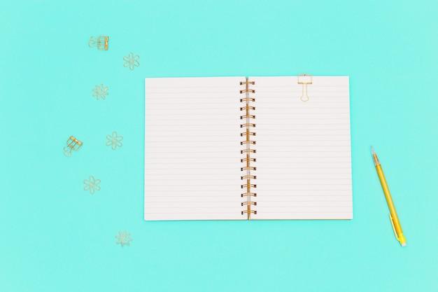 Vista superior da mesa de trabalho com o caderno aberto na primavera, lápis de cor amarela, clipes de metal dourados para papel e documentos. postura plana com artigos de papelaria para escola, educação.