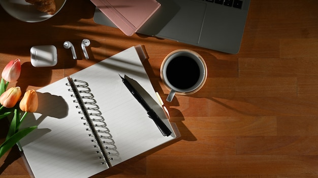 Vista superior da mesa de trabalho com o caderno em branco aberto