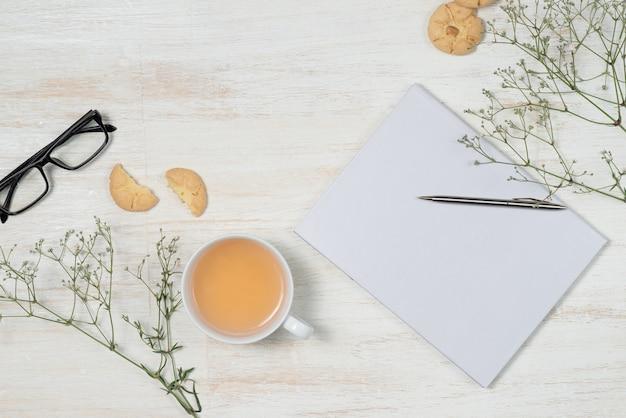 Vista superior da mesa de trabalho com o caderno em branco com caneta, xícara de café, telefone celular e biscoitos no fundo de madeira