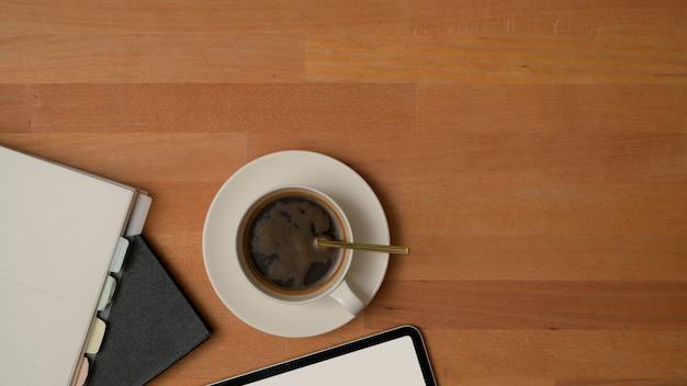 Vista superior da mesa de trabalho com uma xícara de café, cadernos, tablet de simulação e espaço de cópia na mesa de madeira