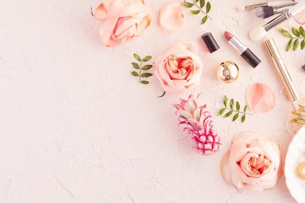 Vista superior da mesa de trabalho de blogueiro de beleza de mulher com cosméticos decorativos, flores e folhas de palmeira, prato de folha, envelope na mesa pastel rosa