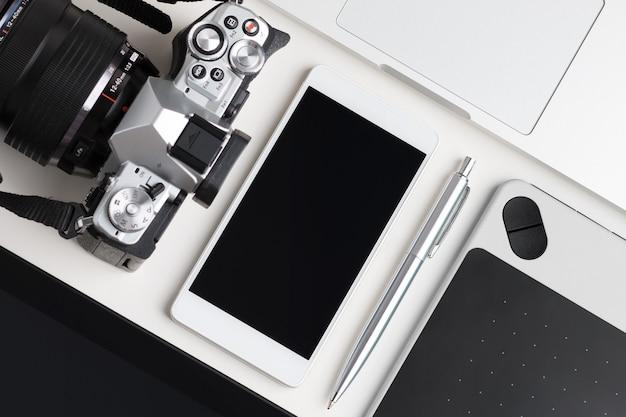 Vista superior da mesa de trabalho do designer, blogueiro ou fotógrafo. tablet gráfico, tablet pc, laptop, smartphone e câmera fotográfica deitado na mesa branca.