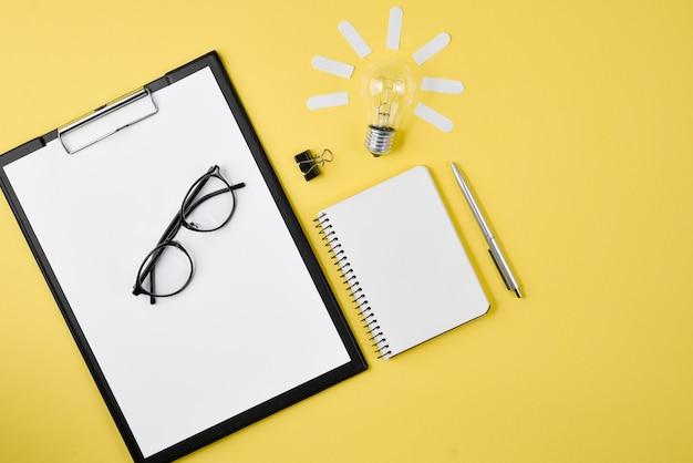 Vista superior da mesa de trabalho estilo design de material de escritório com caneta, bloco de notas, óculos, lâmpada