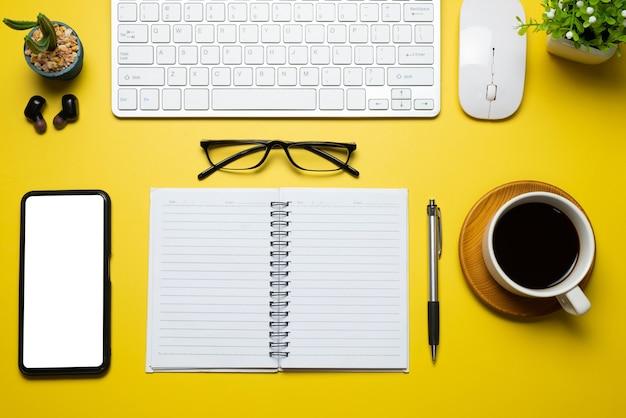Vista superior da mesa de trabalho moderno equipamento smartphone tela branca em branco