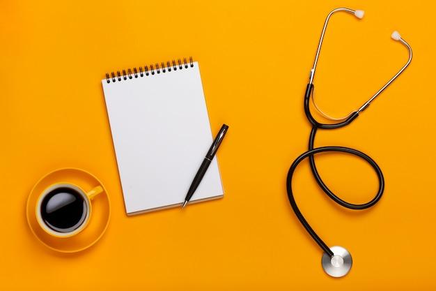 Vista superior da mesa de um médico com bloco de notas e caneta estetoscópio, teclado, prescrição e pílulas, uma xícara de café sobre um fundo amarelo