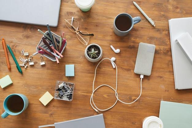 Vista superior da mesa desordenada do local de trabalho com xícaras, canecas e artigos de papelaria, trabalho em equipe ou conceito de estudo