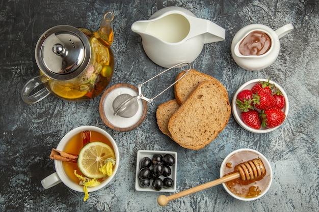 Vista superior da mesa do café da manhã pão mel e chá na superfície escura.