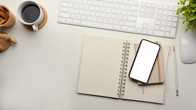 Vista superior da mesa do computador com papelaria teclado smartphone e traçado de recorte da xícara de café