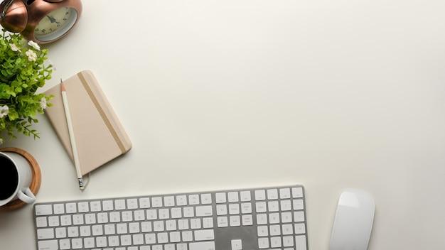 Vista superior da mesa do computador com teclado, mouse, livro de leite, xícara de café, decorações e espaço de cópia