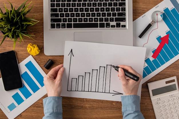 Vista superior da mesa do escritório com calculadora e gráfico de crescimento