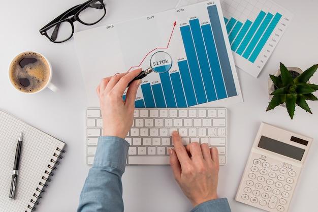 Vista superior da mesa do escritório com gráfico de crescimento analisado com lupa