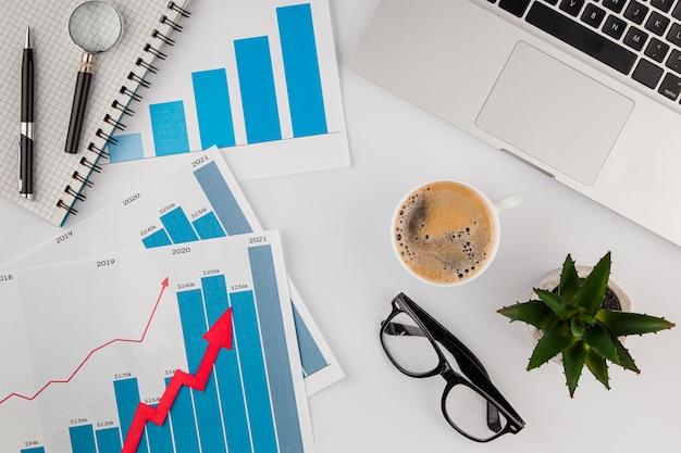 Vista superior da mesa do escritório com gráfico de crescimento e café com óculos