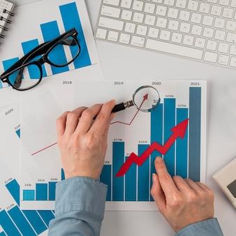 Vista superior da mesa do escritório com gráfico de crescimento e mãos segurando uma lupa