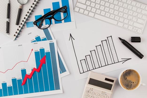 Vista superior da mesa do escritório com gráfico de crescimento e óculos