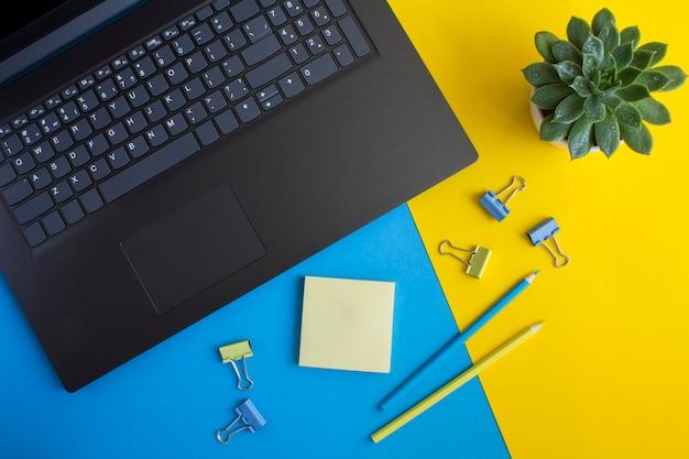 Vista superior da mesa do escritório com laptop, cacto e papelaria