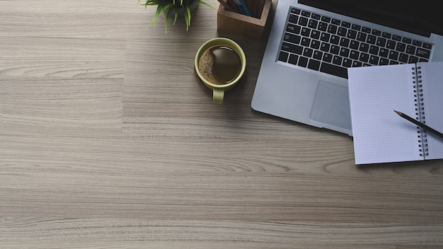Vista superior da mesa do escritório em casa com laptop, notebook e xícara de café na mesa de madeira