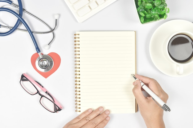 Vista superior da mesa do médico com as mãos escrevendo algo no caderno em branco