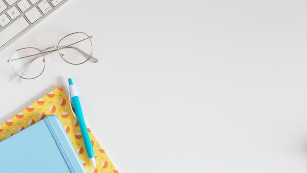 Vista superior da mesa infantil com notebooks e óculos
