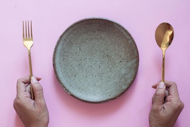 Vista superior da mesa, mãos de mulher segurando um garfo e colher com prato vazio em fundo rosa