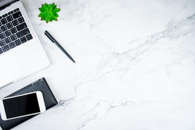 Vista superior da mesa moderna de um jovem com um laptop, smartphone, bolsa de couro e acessórios