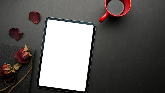 Vista superior da mesa preta com tablet digital, caderno, rosas secas, caneca de café e espaço de cópia, traçado de recorte