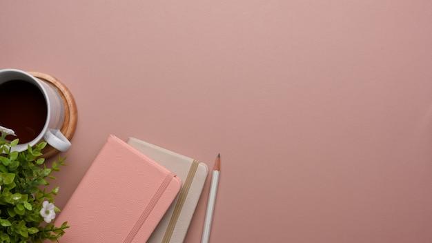 Vista superior da mesa rosa com livros de laticínios, lápis, vaso de plantas, xícara de café e espaço de cópia, simulação de cena