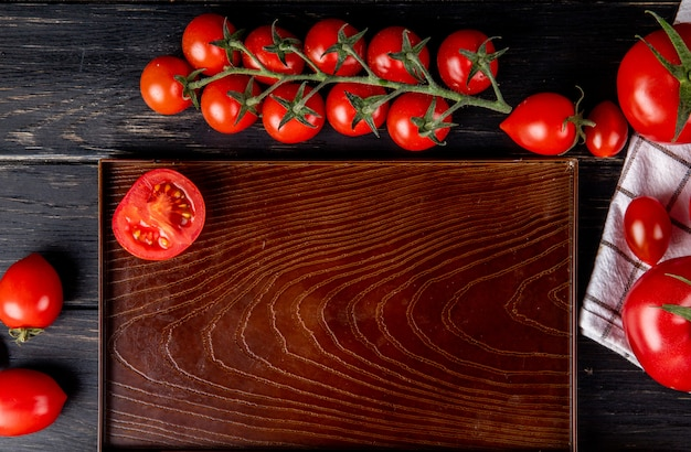 Vista superior da metade cortada tomate na bandeja e os inteiros na superfície de madeira