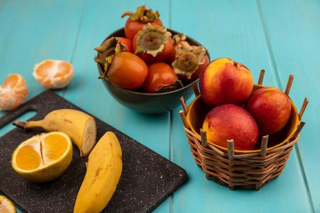 Vista superior da metade de bananas frescas em uma placa de cozinha preta com caquis em uma tigela com pêssegos em um balde em uma parede de madeira azul