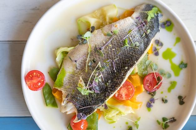 Vista superior da metade do peixe assado decorado com tomates cereja fatias de pepino e microgreen Foto Premium