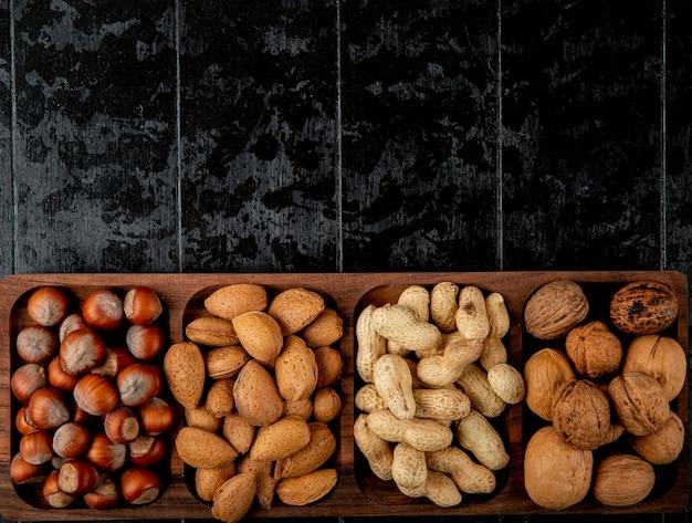 Vista superior da mistura de nozes avelãs amêndoas e amendoins com casca em fundo preto com espaço de cópia