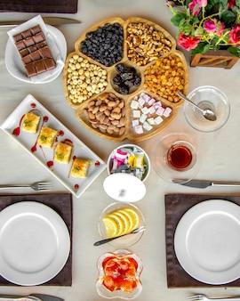 Vista superior da mistura de nozes com frutas secas em um prato de madeira servido com chá e doces nacionais em cima da mesa