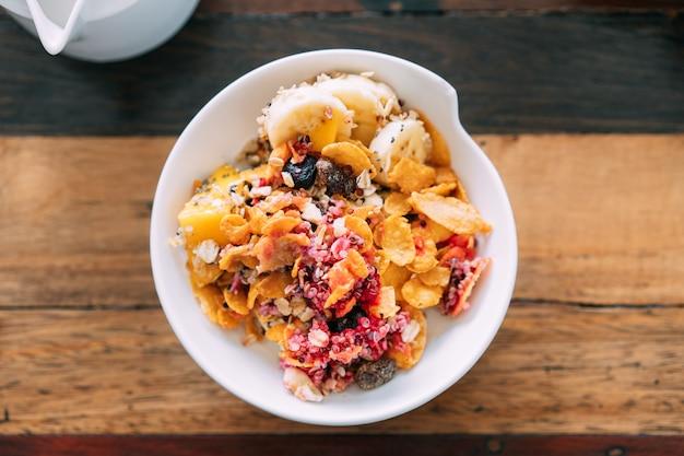 Vista superior da mistura de tigela de açaí com manga fresca, abacate, banana e frutas vermelhas