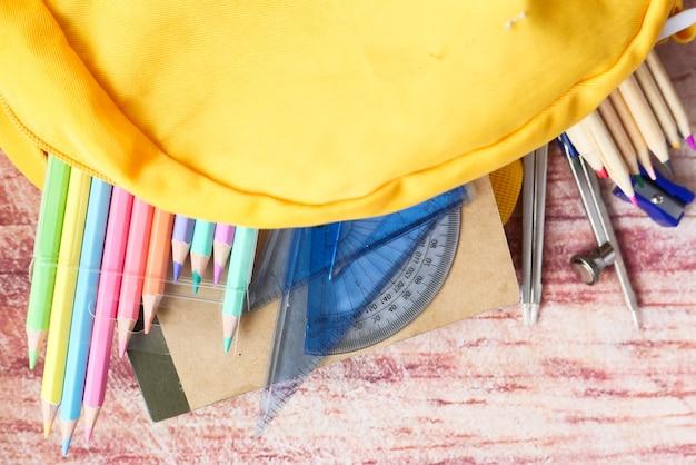 Vista superior da mochila amarela com diferentes artigos de papelaria coloridos na mesa