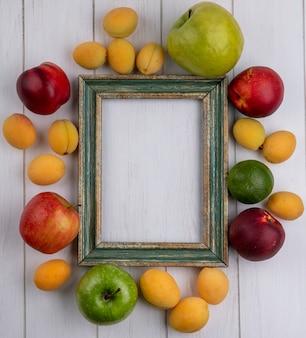 Vista superior da moldura amarela esverdeada com pêssegos, maçãs e damascos em uma superfície branca