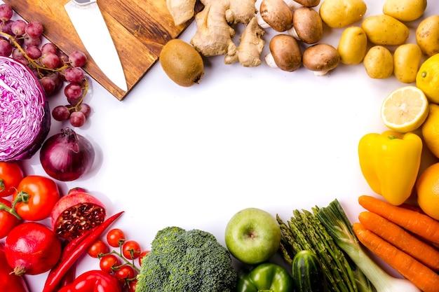 Vista superior da moldura cheia de vegetais frescos coloridos em um fundo branco, ideal para uma dieta balanceada