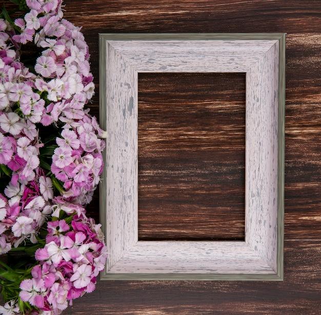 Vista superior da moldura cinza com flores rosa claras em uma superfície de madeira