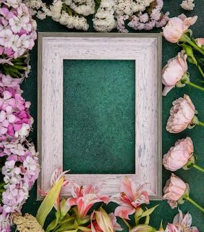 Vista superior da moldura cinza com flores rosa claro em uma superfície verde