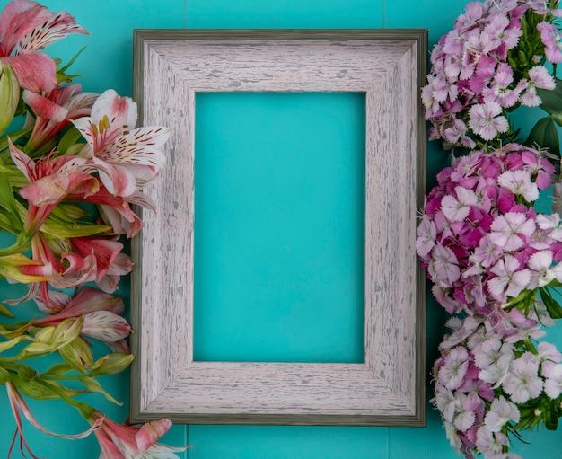 Vista superior da moldura cinza com flores roxas claras e lírios rosa em uma superfície azul clara