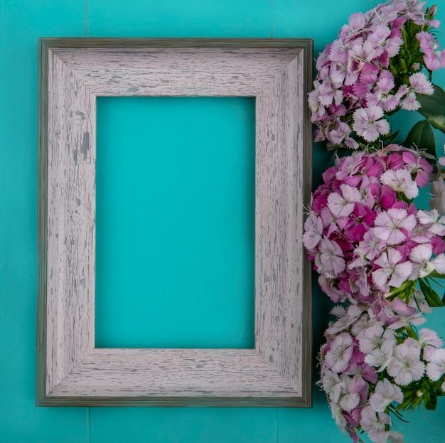Vista superior da moldura cinza com flores roxas claras em uma superfície azul clara
