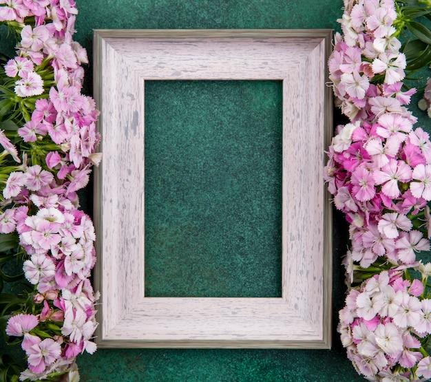 Vista superior da moldura cinza com flores roxas claras em uma superfície verde