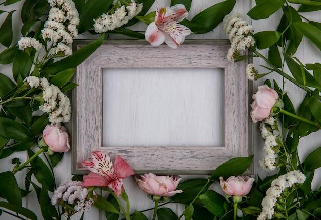 Vista superior da moldura cinza com galhos de folhas e flores rosa claro em uma superfície cinza