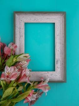 Vista superior da moldura cinza com lírios rosa em uma superfície azul