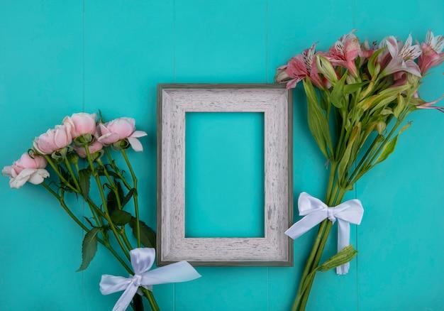 Vista superior da moldura cinza com rosas e lírios rosa claro em uma superfície azul clara