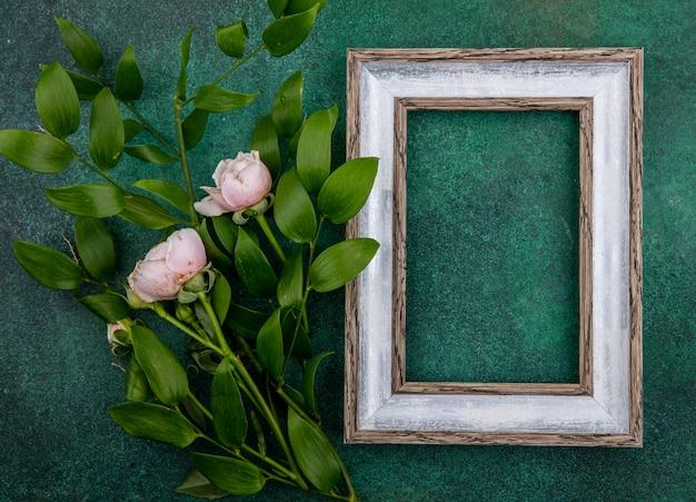 Vista superior da moldura cinza com rosas rosa claras e ramos de folhas em uma superfície verde